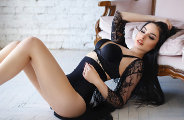 Sensual brunette woman with long hair, posing in sexy black lingerie