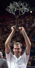 GREG RUSEDSKI OF BRITAIN RAISES TROPHY AT PARIS OPEN.