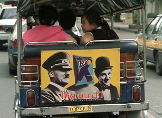 """Two passengers ride on a motor tricycle taxi or """"tuk-tuk"""" pasted with pictures of Adolf Hitler and C.."""