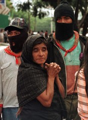 An elderly woman stands with two Zapatista Mayan Indian rebels outside the Church of the Poor in Oax..