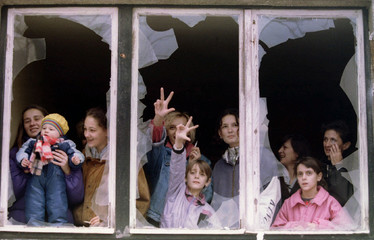 Serbian women and children watch protesters from an appartment building shattered window during a de..