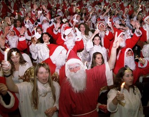 """Dozens of Santa Clauses and Christmas angels wave with their candles while singing """"Jingle Bells"""" la.."""