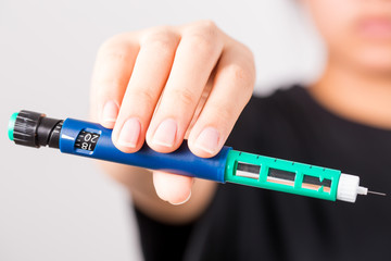 patient holding insulin pen prepare to use