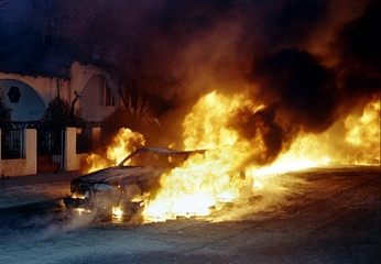 A car is engulfed in flames as oil from an underground pipeline burns in background in San Fernando,..