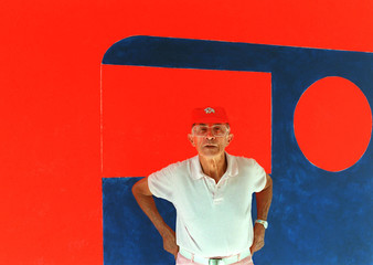 French fashion designer Andre Courreges stands near one of his paintings above his fashion workshops..