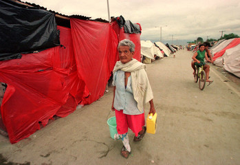 A woman carries water for cooking November 6 in an encampment for people left homeless by floods cau..