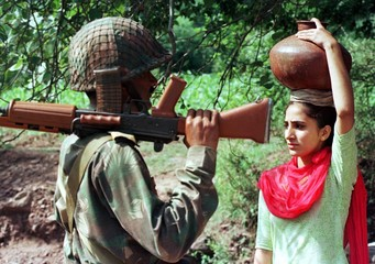 AN INDIAN SOLDIER TALKS TO A VILLAGE GIRL ABOUT HER SAFTY NEAR THE MILiTARY CONTROL LINE DIVIDING ...