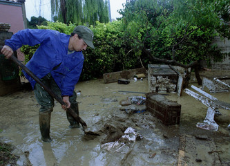 A man cleans up his yard after flood waters swept through this town in southern France Sept 23..