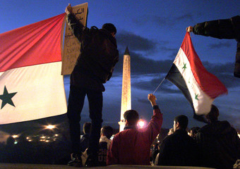 Protester wave Iraq's national flags in front of the Louqsor obelisk at Concorde square December 19...