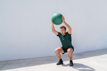 Squat with overhead medicine ball throw or shoulder press. Weight exercises workout fitness man training legs and glutes with weighted medicine ball squats. Athlete working out at gym.