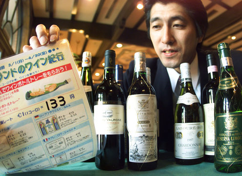BEER HALL ASSISTANT MANAGER HOLDS UP EUROPEAN WINE MENU WITH EURO PRICES IN TOKYO.