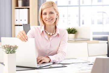 Happy female receptionist with laptop computer