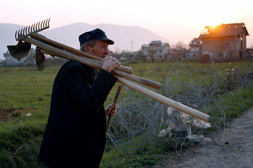 An elderly Sarajevan carries garden tools as he goes to dig a kitchen garden in the former front lin..