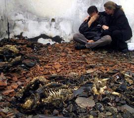 Ethnic Albanian Lule Berisha (R) comforts her cousin Petrit Berisha, who lives in the German town of..