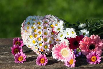 Alles Liebe mit einem Herz aus Gänseblümchen mit Margeriten und Gerbera auf Holz