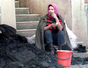 A Bosnian woman takes a cigarette break from stocking up on coal for winter outside of her appartmen..