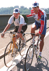 Four-time Tour de France winner Miguel Indurain of Spain (R) greets a local youngster while previewi..