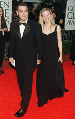 Actor George Clooney arrives with his girlfriend, French model Celine Balitran at the 55th annual Go..