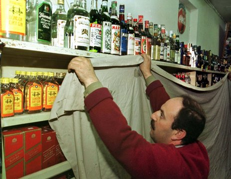 Ismail, a Jordanian liquor store worker cover shelves of alcoholic drinks at a supermarket in Amman ..