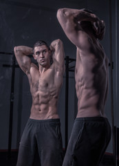 bodybuilder posing, looking at himself, double mirror image