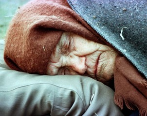 ELDERLY ETHNIC ALBANIAN WOMAN SLEEPS AT A CAMP FOR REFUGEES.