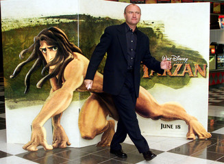 """Musician Phil Collins clowns around in front of a poster for the new Disney film """"Tarzan"""" as he arri.."""