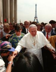 A girl kisses the hand of Pope John Paul II in Paris