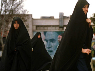Iranian girls walk in front of a billboard featuring the late founder of the Islamic revolution Ayat..