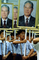Taiwanese high school students hold pictures of President Lee Teng-hui in Taipei October 5 at a rehe..
