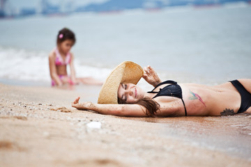 Woman and little girl relaxing on the beach