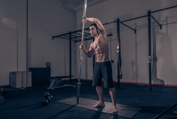 one young man, bodybuilder posing holding bar vertical