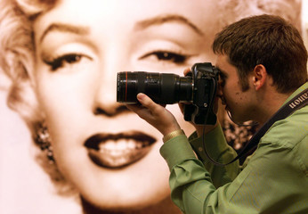A PHOTOGRAPHER TAKES A PICTURE AT THE MARILYN MONROE EXHIBITION IN LONDON.