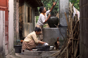 WOMEN CLEAN DISHES WITH WATER FROM WELL IN YOGYAKARTA.