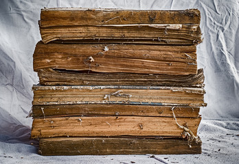 Old books stacked on dirty white cloth