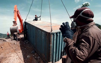 Cambodian workers remove toxic waste dumped in Cambodia by a Tawainese firm from a site in Sihanoukv..