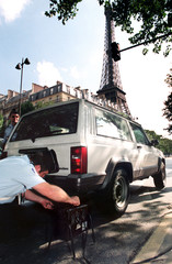A policeman checks pollution from a car in front of the Eiffel tower August 13.Paris police lowered ..