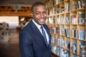 Happy smile from handsome african american legal professional at office firm hall with bookshelves