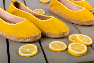 Yellow espadrilles shoes near slices of lemon on wooden background. Close up.