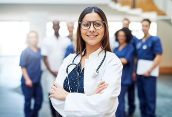 Young ethnic female doctor standing in clinic in front of team