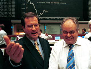 Germany's Foreign Minister Klaus Kinkel (L) gestures beside Rainer Roubal, a stock exchange trader, ..
