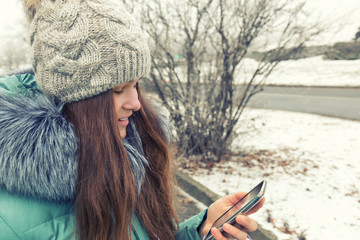 Pretty girl doing a selfie with her smart phone. Beautiful young woman. Outdoor winter portrait. Beautiful smiling girl talking on cell phone in snowy winter park. Toned and processing photo