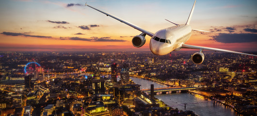 Passengers airplane flying above London city in the sunset light Wall mural