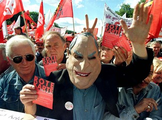 "Demonstrators, one wearing a mask of German Chancellor Helmut Kohl, show cards saying ""Red card, Mis.."