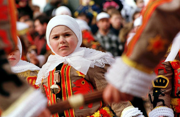 A little boy dressed as a Gille of Binche, resplendent in his red, yellow and black mediaeval costum..