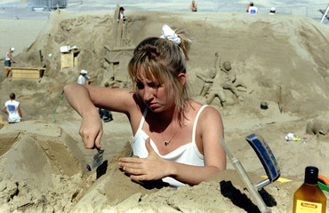A sculptor works on a giant sand castle August 11 on the beach of Zeebruges at the Belgian coast. Th..