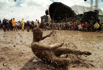 Phil Johnson from Bristol skids around in the mud next to the Pyramid stage on the second day of the..