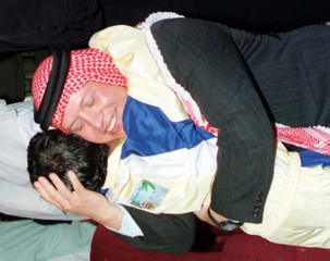 KING ABDULLAH EMBRACES CHILD AT ORPHANAGE.