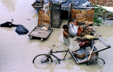 A resident in a slum area in the Indian capital New Delhi collects his belongings from his flooded h..