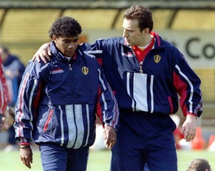 Belgian midfielder Marc Wilmots (R) puts his arm around the shoulder of his team-mate Luis Oliveira ..
