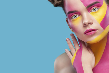 Portrait of the bright beautiful girl with art colorful painting make-up and bodyart. Copy space.